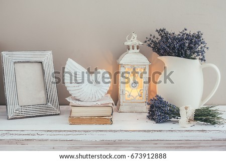 Shabby chic interior decor for farmhouse. Lavender in pitcher, books and lantern on a vintage shelf over pastel wall. Provence home decoration. #673912888