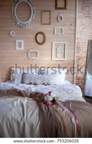 Shabby chic interior decor The bedroom is in the style of Provence wooden wall decorated with photo frames.