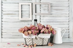 Shabby chic still life: bunch of vintage pink dry roses in wire basket and jug against white wooden blinds with empty photoframes.