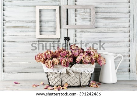 Shabby chic still life: bunch of vintage pink dry roses in wire basket and jug against white wooden blinds with empty photoframes. #391242466