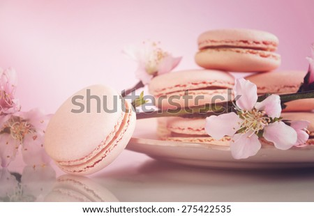 Shabby chic vintage style pink macarons on white reflective table and pink Spring blossom, with applied retro style filters and added lens flare light beam.