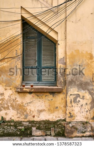 Shabby facade of old house with window with wooden shutters and power cables in Hanoi in Vietnam. Two plastic cups are on the windowsill. Vertical.