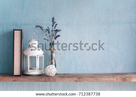 Shabby old interior decor for farmhouse. Lavender in glass vase and book,candle on a vintage shelf over pastel wall. Home decoration.