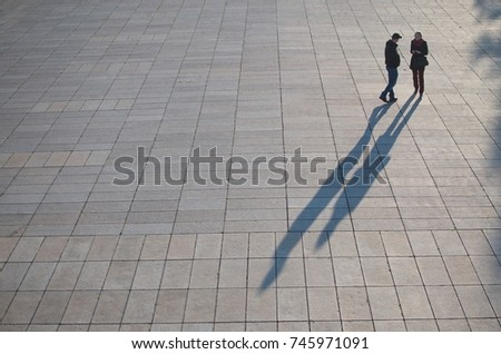 Shades of people standing on a pavement square #745971091