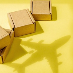 Shadow Airplane and stack of cardboard boxes. concept of air cargo and parcels, airmail. Fast delivery of goods and products. Cargo aircraft. Logistics, connection to hard-to-reach places. Banner