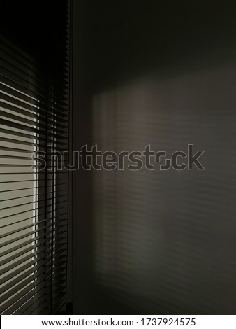 Shadow and light through blinds window on tiled wall. Abstract form morning light and shadow on the wall.selective focus.