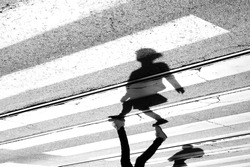 Shadow and silhouette of a teenage girl crossing the street at zebra crosswalk , upside down in black and white