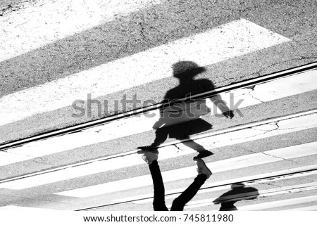 Shadow and silhouette of a teenage girl crossing the street at zebra crosswalk , upside down in black and white #745811980