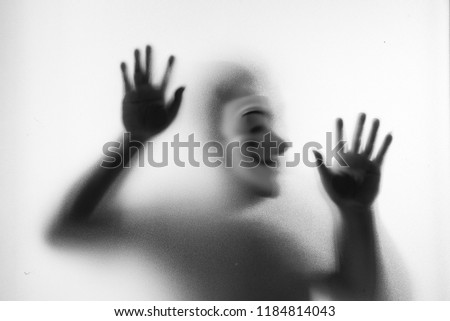 Shadow blur of horror man in fancy mask.Hands on the glass.Dangerous man behind the frosted glass.Mystery man.Halloween background.Black and white picture.Blur picture.