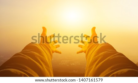 Shadow & blurred photo,A young man prayed for God's blessings with the power and holiness of God on the background of the morning sunrise over the high mountains. God and Spiritual Concepts.