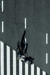Shadow casts on zebra crossing in shape vertical biker riding cross the street
