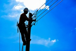 Shadow electricians repairing wire on electric power pole at the blue sky background blur.