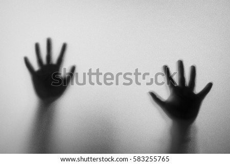 Stock Photo Shadow hands of the Man behind frosted glass.Blurry hand abstraction.Halloween background.Black and white picture.Blur picture.