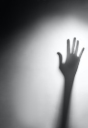 Shadow of a blurry hand behind white frosted glass, film. The concept of dangerous, scary, help, horror and fear.