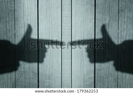 Shadow of a hand with a index finger on the natural wooden background, with space for text or image #179362253