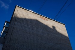 Shadow of a living block reflected on the brick wall of another living block in Balashikha, Russia. Sunny day view.