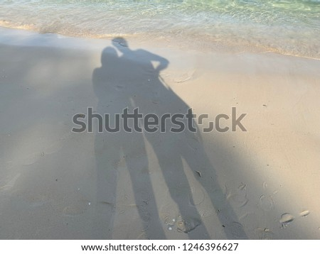 Shadow of a man and woman standing holding hands on sand at beach #1246396627