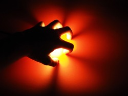 Shadow of a man's hand with yellow light on a red background. Create a flower from the light.