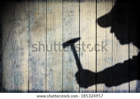 Shadow of a man with hammer in hand on natural wooden background. You can see more silhouettes and shadows on my page.  #185324957