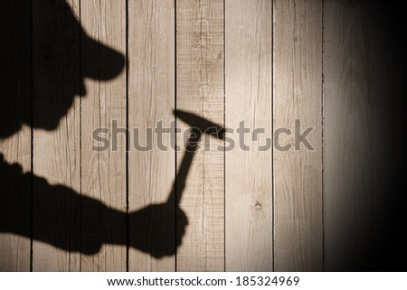 Shadow of a man with hammer in hand on natural wooden background. You can see more silhouettes and shadows on my page.  #185324969