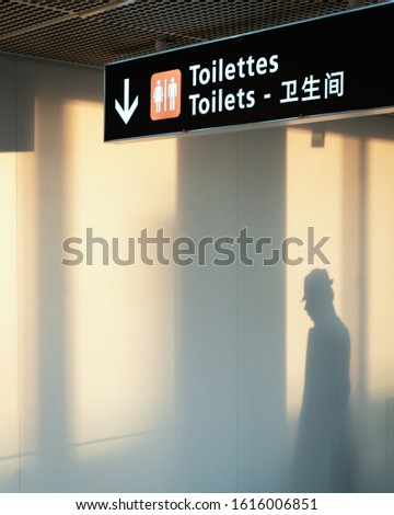 Shadow of a mysterious man under Toilets sign