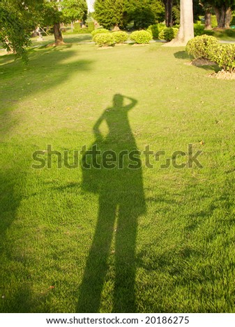 Shadow of a people on the green grass.