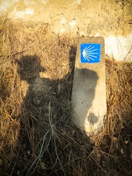 Shadow of a Pilgrim and a Camino de Santiago Way Marker with the Shell and Yellow Arrow, outside Torres del Rio
