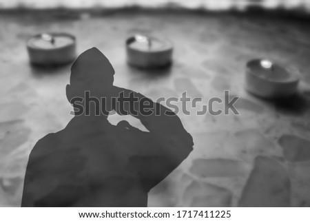 Shadow of a soldier Israel Defense Forces, IDF with salutes on Headstone , on Monument on cemetery, with burning funeral candles. Image for Memorial day Yom ha Zikaron or Yom ha Shoah Stock photo ©