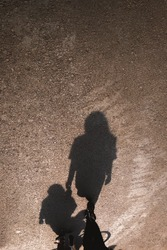 Shadow of a young mother and her child walking on the asphalt road. Happy mother's day