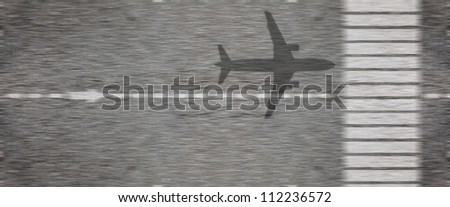 Shadow of an airplane taking off from an airport runway tarmac at high speed.