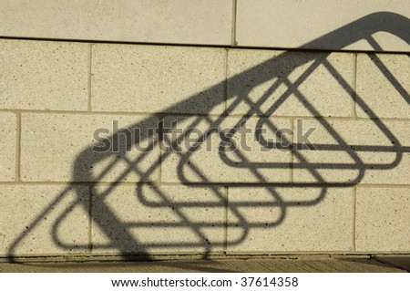 Shadow of bicycle stand on brick wall of public library