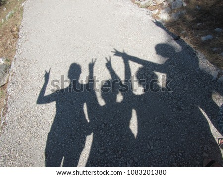 Shadow of four young women on a gravel pathway in a Mediterranean setting - Croatia