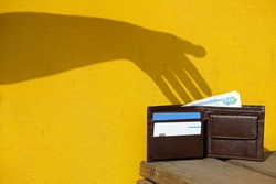 Shadow of hand on yellow wall trying to steal a leather wallet with money, banknote and credit cards. Robber pickpocket silhouette. Concept of financial crime, tax burden, unexpected expenses.