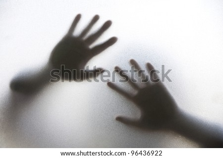 Shadow of  hands for help behind frosted glass in the back light.