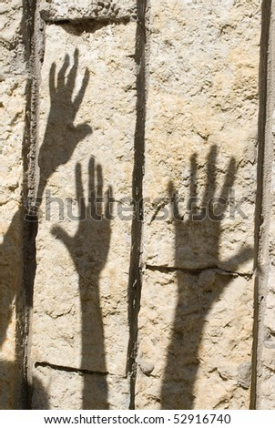 Shadow of humans hand on the stone wall