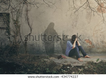 Shadow of Jesus comforts a sad woman.