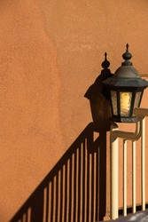 Shadow of lamp and railing on blank orange pink concrete cement exterior  textured urban wall vertical format room for type