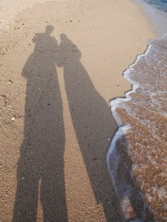 Shadow of male and female couple on the sand of the beach.