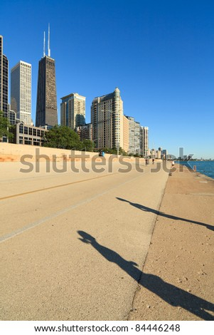 Shadow of male and female joggers running along Lake Michigan on Lakeshore Trail in the early morning in Chicago.