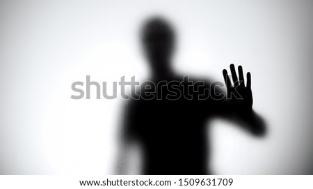 Shadow of man holding glass wall, trying to escape from captivity, kidnapping Stock photo ©