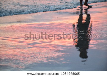shadow of man in beautiful light sunset at the shoreline ストックフォト ©