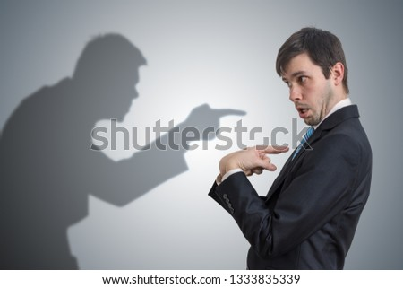 Shadow of man is pointing and blaming businessman. Conscience concept. Stock photo ©