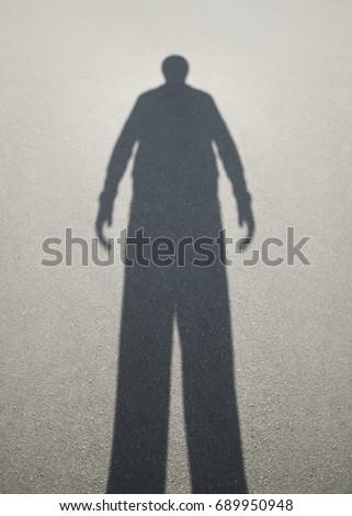 Shadow of man on the asphalt                                #689950948