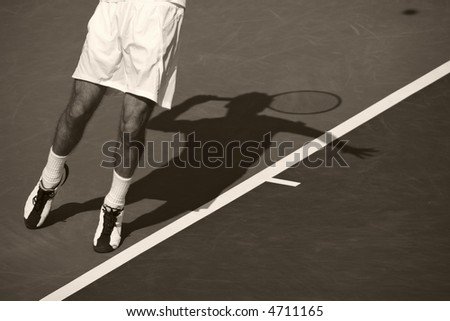 Shadow of man serving a tennis ball.