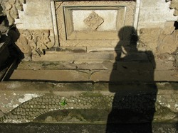 Shadow of man taking a photo at Hindu temple.