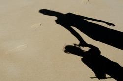Shadow of mother and daughter holding hands on sandy beach during summer holiday vacation. Concept photo of: Mothers day, family relationship, child care, childhood, motherhood, parenthood.Copy space