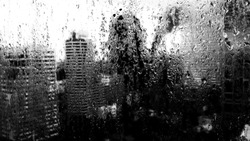 Shadow of oneself looking to a wet and misery day through raindrops-covered window. High contrast black and white image.