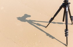 Shadow of photo camera on tripod. The shoot process on sand beach background. Shadow of a camera on the sand with a tripod shadow seen from above.