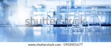 shadow of scientist and glass flask and cylinder equipment in medical science lab blue banner background Stock fotó ©