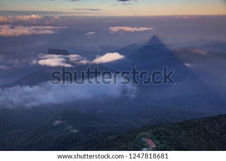 shadow of the conical mountain Adam's Peak or Sri Pada at sunrise - sacred buddhist place. Sri Lanka